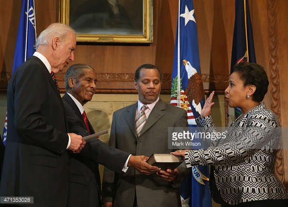 Washington, D.C. – at the Justice Department, Monday, April 27, 2015: U.S. Vice-President Joe Biden (L) swears in Loretta E. Lynch (R) as Attorney General as her husband Stephen Hargrove (2R) and father Lorenzo Lynch (2L) look on. Lynch becomes the 83rd Attorney General, replacing Eric H. Holder. (Photo, credit by Mark Wilson/Getty Images)
